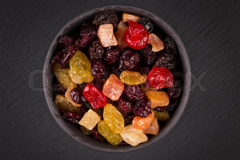 Stock image of 'Mix variety of dried fruit in bowl over black dark stone background'