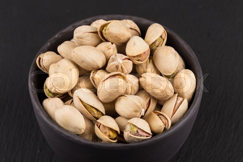 Stock image of 'Pistachio nuts in stone bowl on dark background'