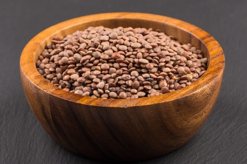 Stock image of 'Organic lentils in bowl on a dark background - close up shot'