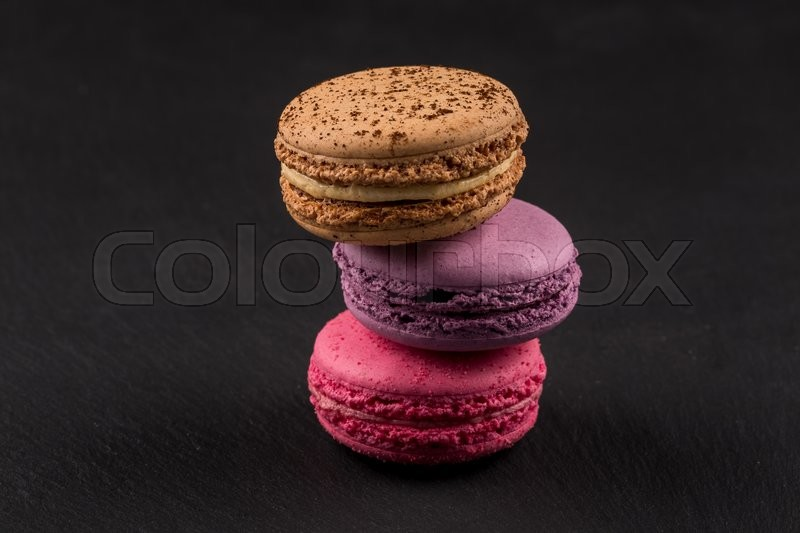 Stock image of 'Tasty colorful macaroons on dark stone background'