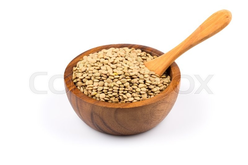 Stock image of 'French green lentils (lentilles du Puy) in a wooden bowl on a white background'