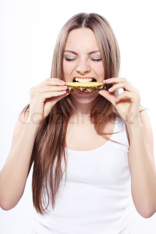 Stock image of 'Girl eating a paneapple isolated on white '