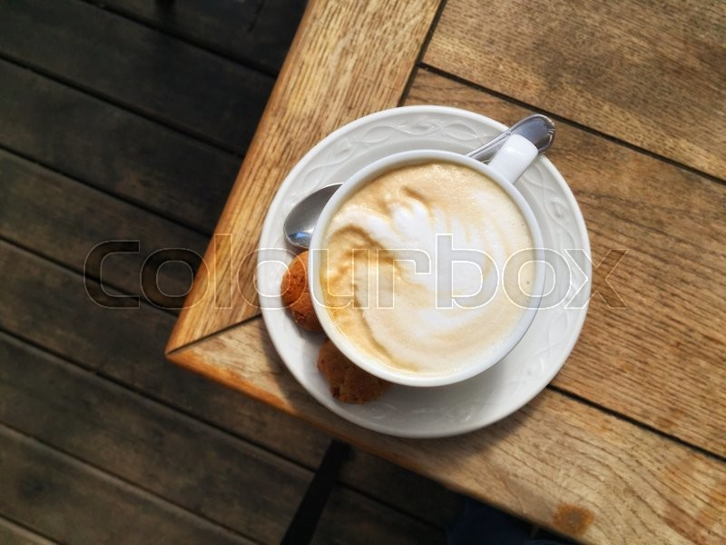Stock image of 'cup of cappuccino on wooden table, top view'