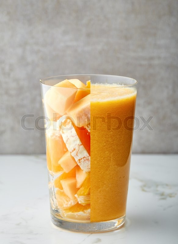 Stock image of 'glass of yellow smoothie on gray kitchen table'