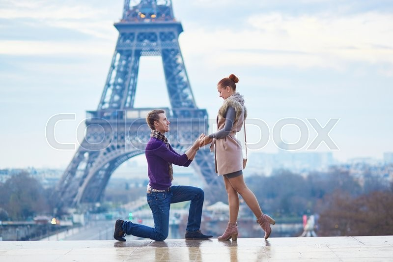 Stock image of 'Romantic engagement in Paris, man proposing to his beautiful girlfriend near the Eiffel tower'