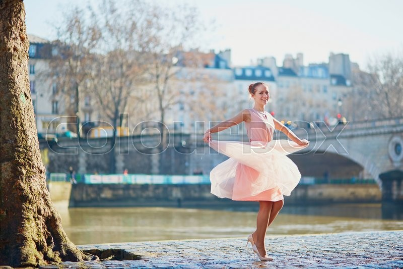 Stock image of 'Beautiful young woman in pink dress dancing in Paris near the river Seine'