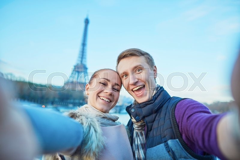 Stock image of 'Happy couple of tourists having fun and taking selfie near the Eiffel tower in Paris'