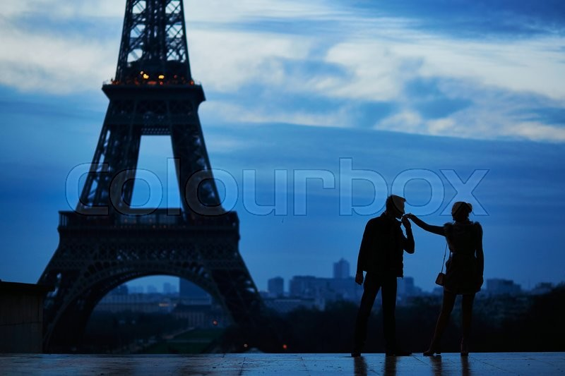 Stock image of 'Silhouettes of young romantic couple near the Eiffel tower in Paris, France'