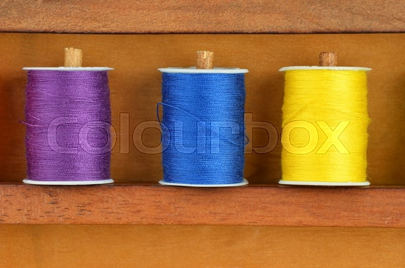 Stock image of 'Sewing kit from color threads in wooden box'
