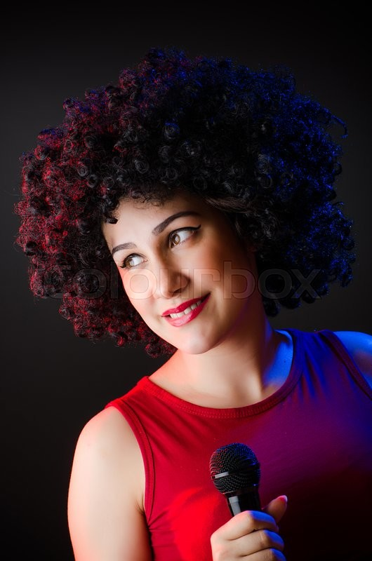 Stock image of 'Woman with afro hairstyle singing in karaoke'