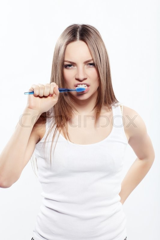 Stock image of 'Girl brushing her teeth isolated on white '