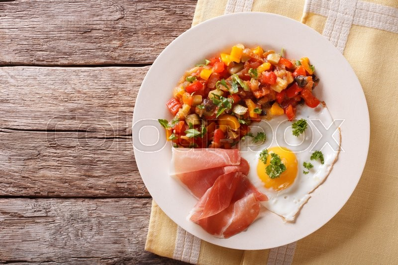 Stock image of 'Healthy breakfast: fried egg, jamon and vegetable stew on a plate close-up. Horizontal view from above\'