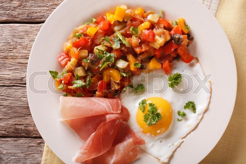 Spanish Food Fried Egg Ham And Vegetables Pisto On The Plate Closeup Horizontal View From Above