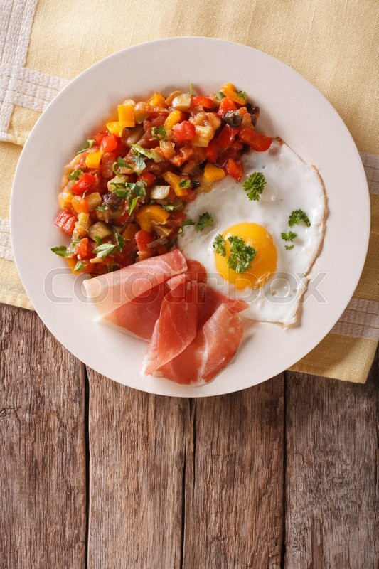 Stock image of 'Spanish Food: fried egg, ham and vegetables Pisto on the plate closeup. Vertical view from above\'