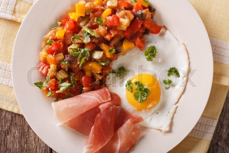 Stock image of 'Spanish breakfast: fried egg, ham and pisto on a plate on the table. Horizontal view from above\'