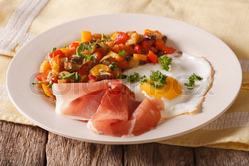 Stock image of 'Spanish cuisine fried egg, jamon and vegetable stew on a plate close-up. horizontal\'