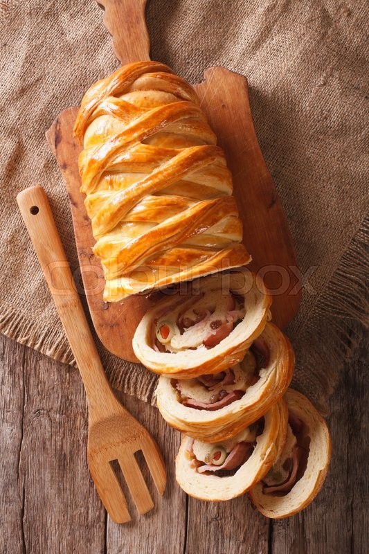 Stock image of 'sliced bread stuffed with ham and olives close-up on the table. Vertical view from above\'