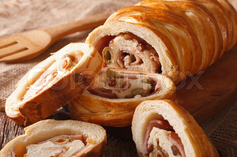 Stock image of 'sliced bread stuffed with ham and olives macro on the table. horizontal\'