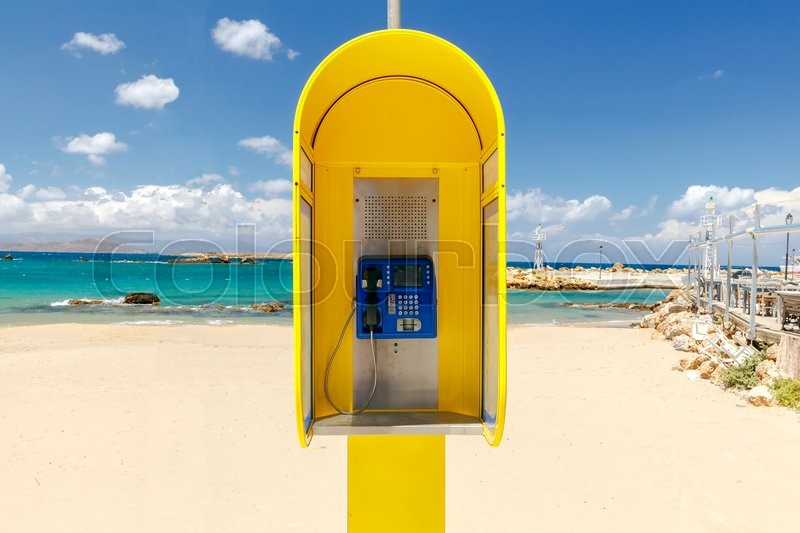 Stock image of 'Yellow phone booth at the beach in Chania.'