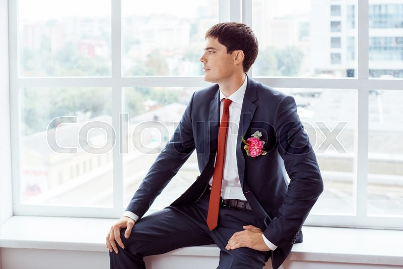 Stock image of 'Gorgeous smiling groom. Handsome man in a suite with a buttonhole sitting on window sill indoors'