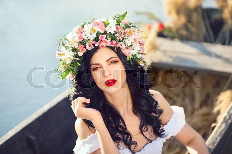 Stock image of 'Portrait of young sexy woman on boat at sunset. The girl has a flower wreath on her head, relaxing and seiling on river. Fantasy art photography. Concept of female beauty, rest in the nature, and travel by water'