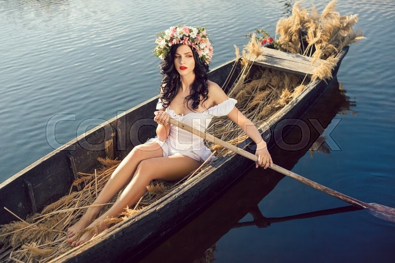 Stock image of 'Young sexy woman sailing on boat at sunset. The girl has a flower wreath on her head, relaxing and seiling on river. Fantasy art photography. Concept of female beauty, rest in the nature, and travel by water'
