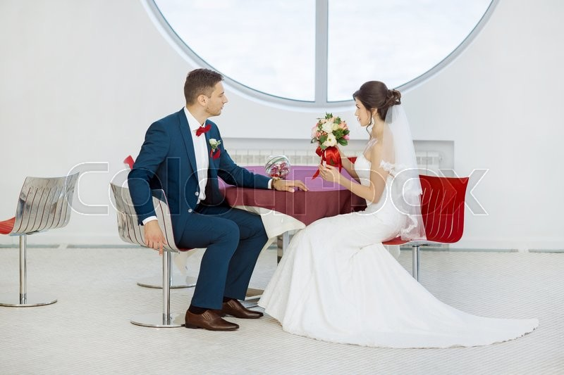 Stock image of 'Wedding couple in love. Beautiful bride in white dress and veil and brides bouquet with handsome groom in blue suit sitting in cafe. Full lenght portrait of man and girl. Concept of wedding celebration in vacation'