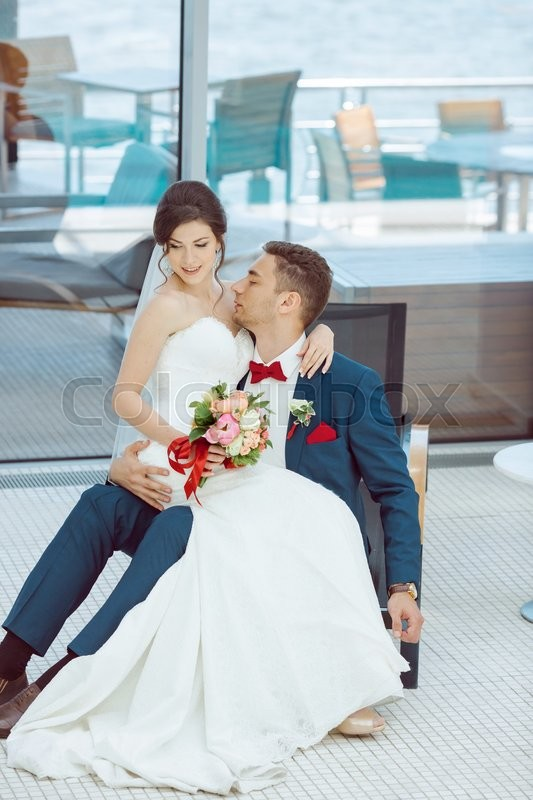 Stock image of 'Wedding couple in love. Beautiful bride in white dress and veil and brides bouquet with handsome groom in blue suit sitting on plank bed and embracing each other indoors at pool. Full lenght portrait of man and girl. Concept of wedding celebration in vacation'