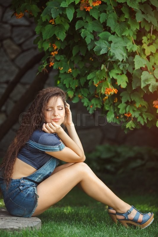 Stock image of 'Beautiful happy young girl in jeans overalls with a hairdress gafra posing in park sitting in the floor and dreaming with closed eyes'