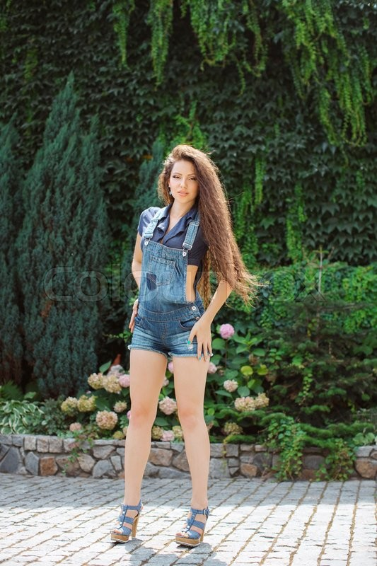 Stock image of 'Beautiful happy young girl in jeans overalls with a hairdress gafra posing in park full body length'