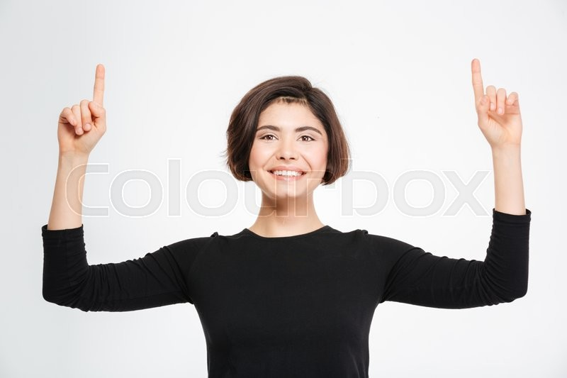 Stock image of 'Happy woman pointing fingers up at copyspace isolated on a white background'