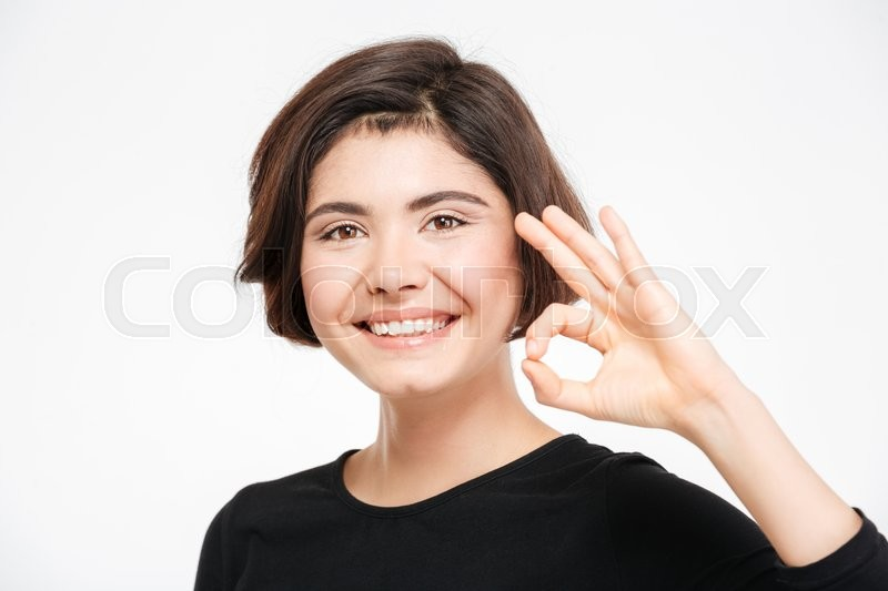 Stock image of 'Smiling woman showing ok sign isolated on a white background'