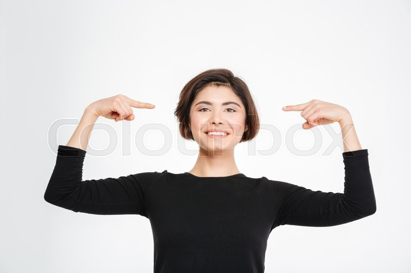 Stock image of 'Smiling woman pointing finger at herself isolated on a white background'