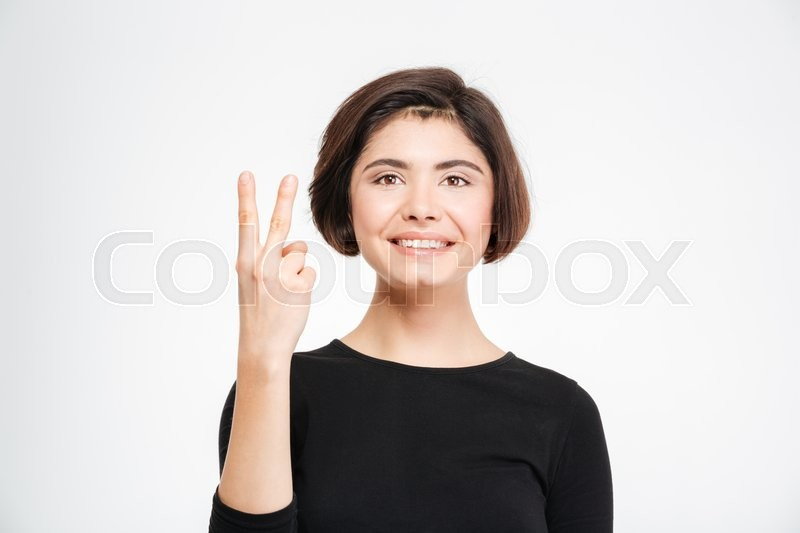 Stock image of 'Smiling woman showing two fingers isolated on a white background'