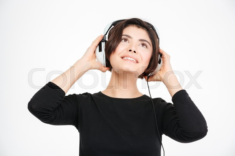 Stock image of 'Happy woman listening music in headphones isolated on a white background'