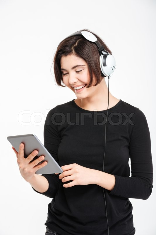 Stock image of 'Happy woman using tablet computer with headphones isolated on a white background'
