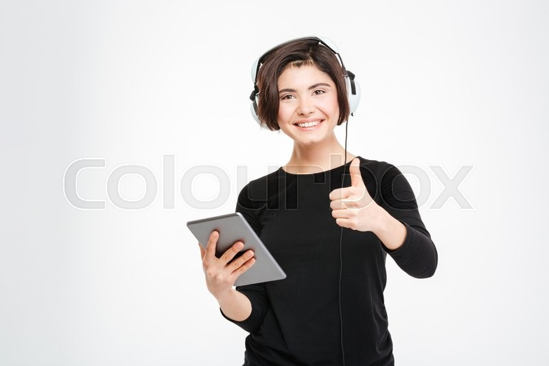 Stock image of 'Smiling woman holding tablet computer and showing thumb up isolated on a white background'