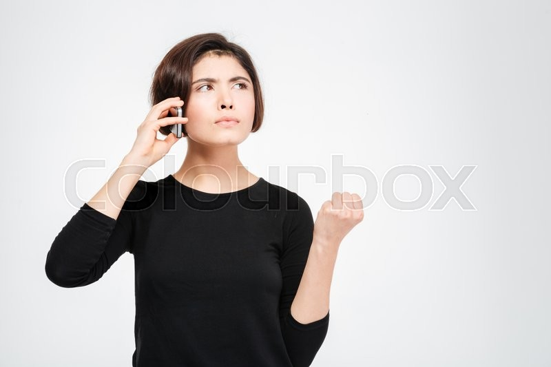 Stock image of 'Angry woman talking on the phone isolated on a white background'