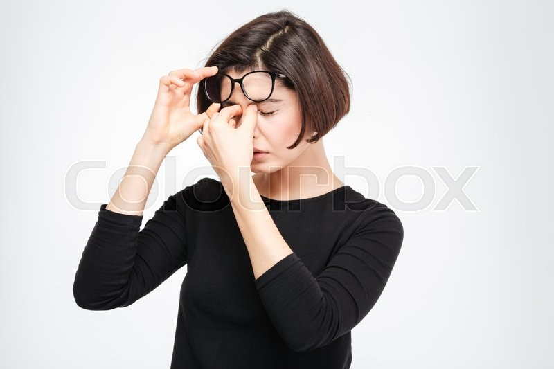 Stock image of 'Young woman rubbing her eyes isolated on a white background'