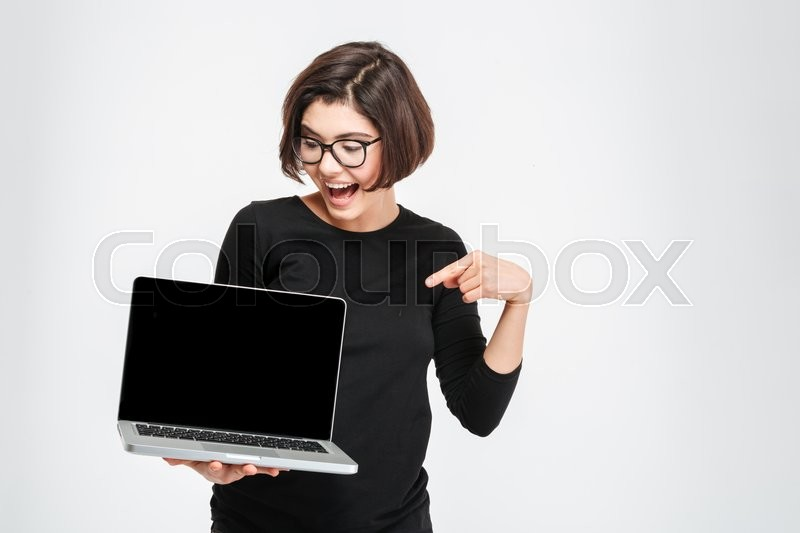 Stock image of 'Cheerful woman pointing finger on blank laptop computer screen isolated on a white background'