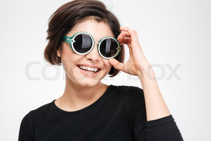 Stock image of 'Smiling woman in sunglasses standing isolated on a white background'
