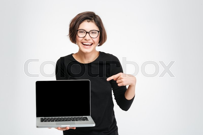 Stock image of 'Laughing woman pointing finger on blank laptop computer screen isolated on a white background'