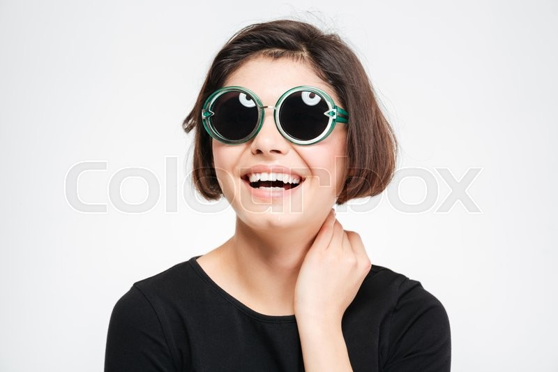 Stock image of 'Laughing woman in sunglasses posing isolated on a white background'