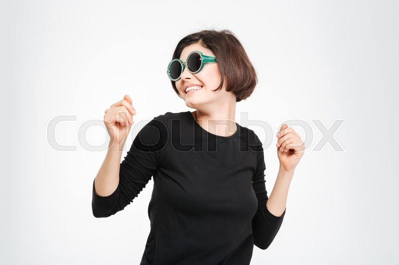 Stock image of 'Smiling woman in sunglasses dancing isolated on a white background'