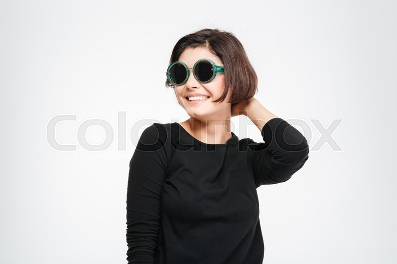 Stock image of 'Happy woman in sunglasses posing isolated on a white background'