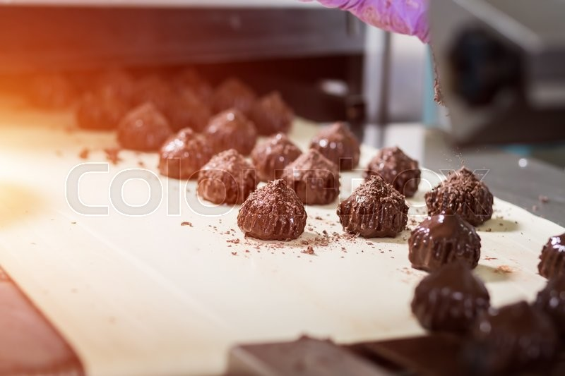 Stock image of 'Brown sweets on beige cloth. Dark candies with shavings. Dream of a gourmet. Special recipe of savoury dessert.'