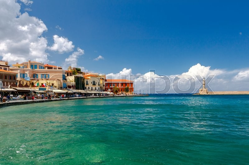Stock image of 'Lighthouse in the old harbor of Chania, on a background of blue sea and clouds.'