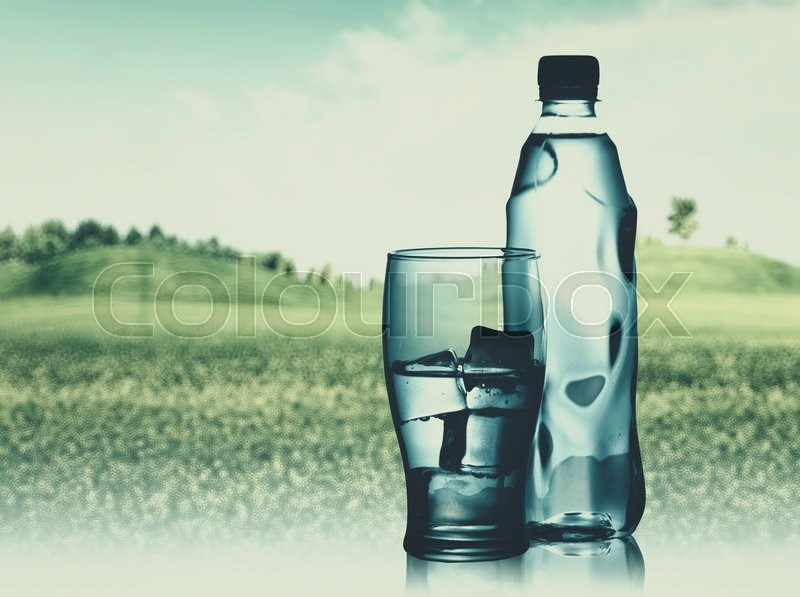 Stock image of 'Bottled spring mineral water against abstract natural backgrounds'