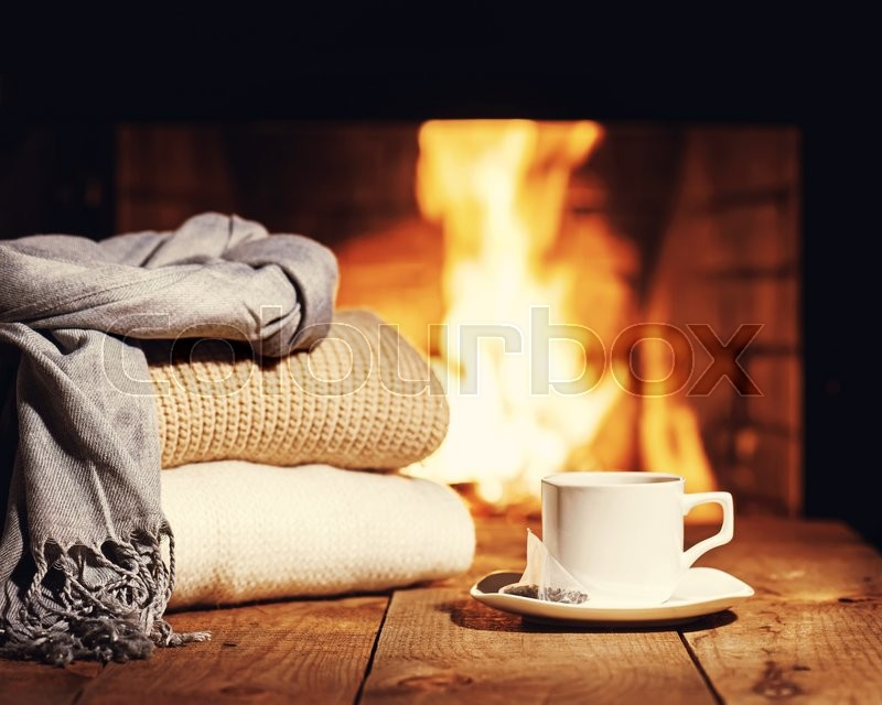 Stock image of 'White cup of tea and warm woolen things near fireplace on wooden table. Winter and Christmas holiday concept. Photo with retro filter effect.'