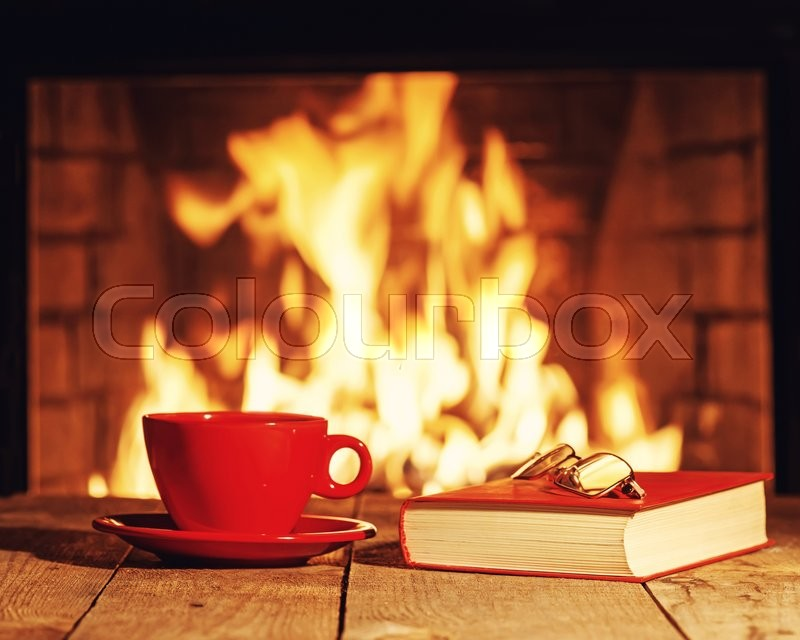 Stock image of 'Red cup of tea or coffee, glasses and old book near fireplace on wooden table. Winter and Christmas holiday concept. Photo with retro filter effect.'